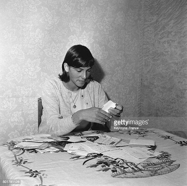 French champion swimmer Christine Caron with all the mail she receives daily from supporters in July 1963 in France