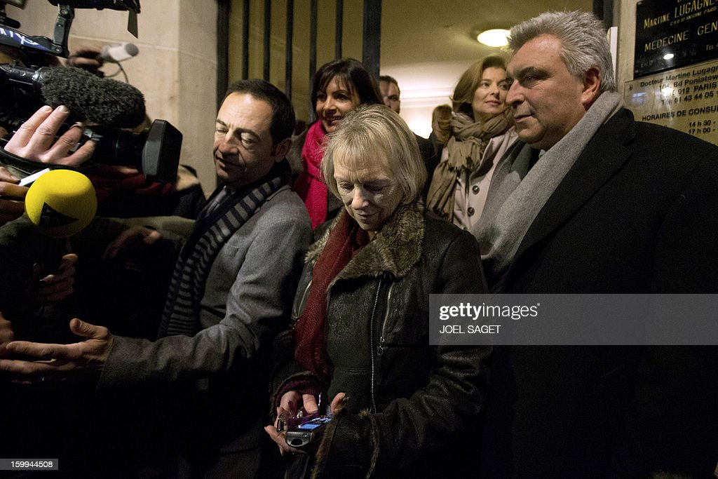 French Charlotte Cassez (C), mother of French national Florence Cassez who was released from prison, flanked by Jean-Luc Romero (L), President of Cassez support comitee, and French minister for Transports and Maritime Economy Frederic Cuvillier (R), answers journalists questions as she looks at her cell phone on January 23, 2013 in Paris. Mexico's Court announced the immediat relax of Florence Cassez.