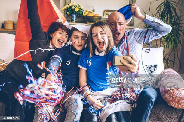 french cheering family watching soccer match on mobile on sofa