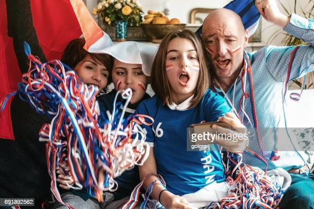 french cheering family watching soccer match on smartphone at home