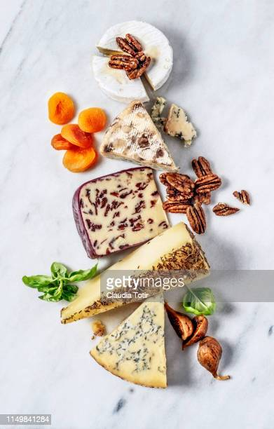 french cheese served with dried fruit, and walnuts on a marble cutting board - kaasplank stockfoto's en -beelden