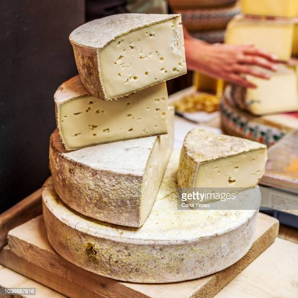 french cheeses on market stall - french culture stock photos and pictures