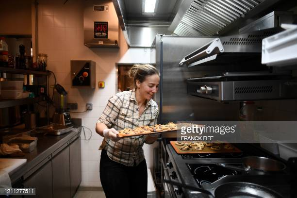 """French Chef Amandine Chaignot checks the baking of cookies as she transformed her Parisian restaurant """"Pouliche"""" into a mini-market to sell gourmet..."""