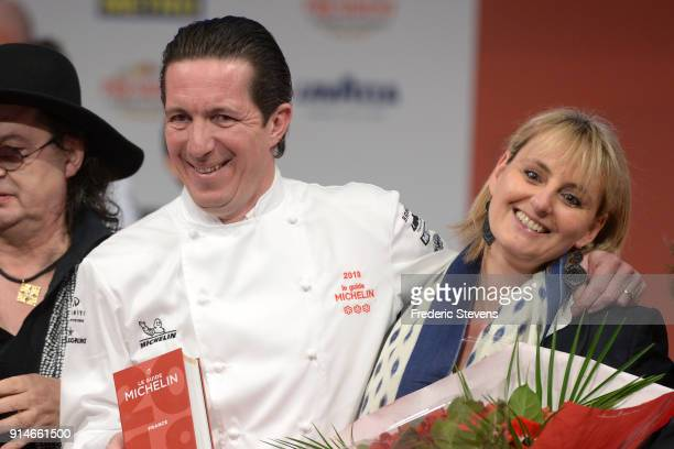 French chef Christophe Bacquie and his wife pose with the 2018 Michelin Guide during the Michelin Award Ceremony 2018 at Philharmonie De Paris on...