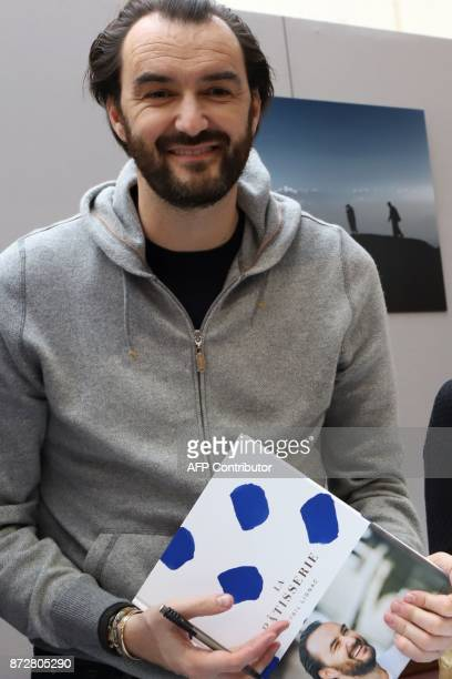 French chef Cyril Lignac poses with his book during the 36th edition of the 'Foire du Livre de Brive' book fair on November 11 2017 in...