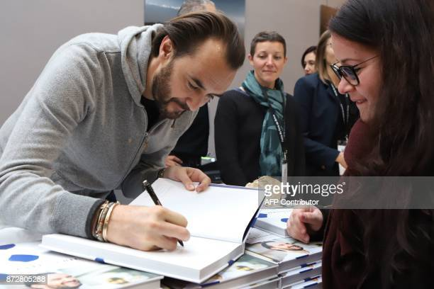 French chef Cyril Lignac signs his book during the 36th edition of the 'Foire du Livre de Brive' book fair on November 11 2017 in BrivelaGaillarde...