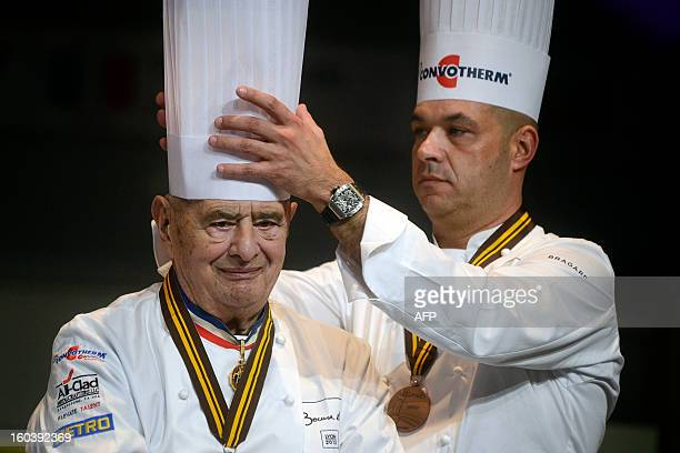French chef Jerome Bocuse adjusts the hat of his father French chef Paul Bocuse at the 14th edition of the world final of the international culinary...