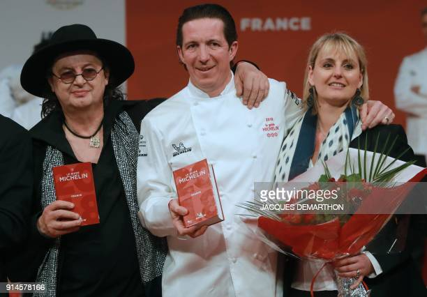 French chef Marc Veyrat and French chef Christophe Bacquie flanked by his wife celebrate after being awarded during the Michelin guide award ceremony...