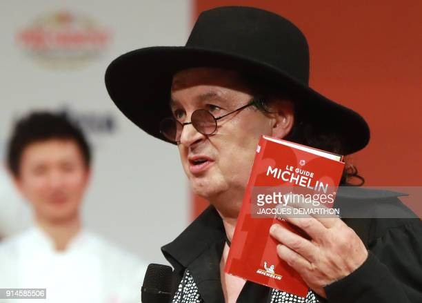 French chef Marc Veyrat holds a Michelin guide after being awarded the maximum three Michelin stars during the Michelin guide award ceremony at La...