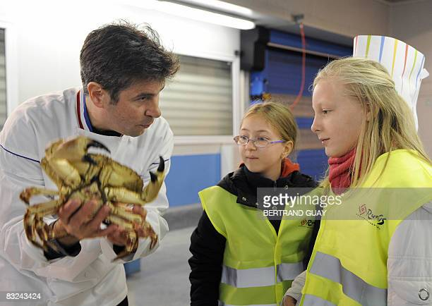 French Chef Michel Roth shows a crab to pupils on October 13 2008 at Rungis wholesale food market outside Paris during a visit as part of the...