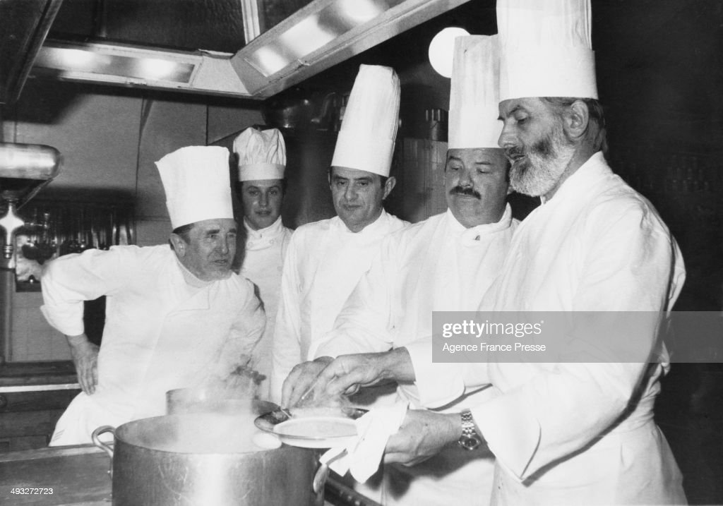 French chef Paul Bocuse (centre) in the kitchens of the Elysee Palace, Paris, after being awarded the Legion of Honour by President Valery Giscard d'Estaing, 25th February 1975. He is helping to prepare a presidential dinner with (left to right) Marcel Le Servot, Chef de cuisine at the Elysee Palace, Mathias Thery, Pierre Troisgros and Jean Troisgros. Bocuse created a special truffle soup for the occasion.