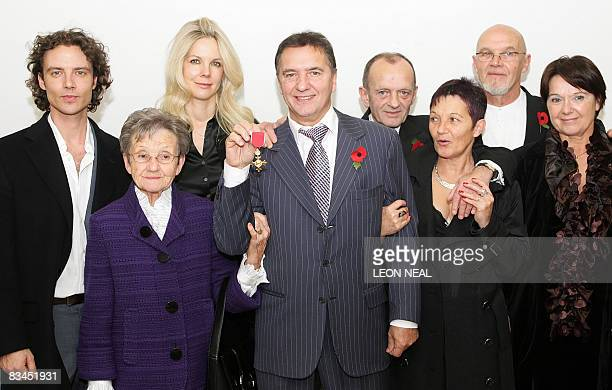 French chef Raymond Blanc poses for photographs with members of his family after receiving his OBE from Britain's Culture Secretary Andy Burnham in...