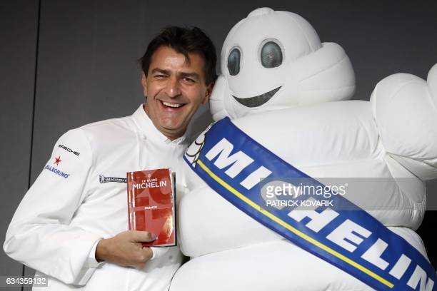 French chef Yannick Alleno poses with the Michelin Man and the Michelin Guide 2017 after having been awarded with three Michelin stars for his Alpine...
