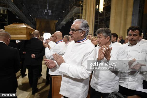 French chefs Alain Ducasse Regis Marcon and French chef Yannick Alleno applaud as the coffin French chef Paul Bocuse leaves the SaintJean Cathedral...