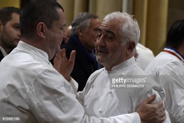 French chefs Christophe Marguin and Guy Savoy talk as they arrive to attend the funeral ceremony for French chef Paul Bocuse at the SaintJean...