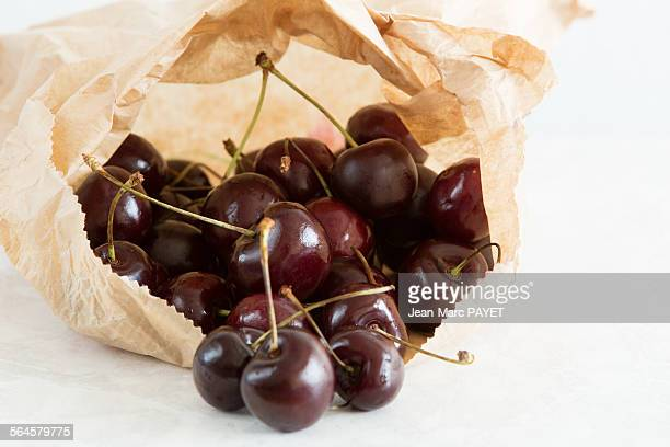 french cherries in a paper bag - jean marc payet foto e immagini stock