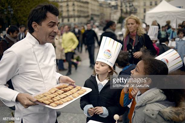French chief Yannick Alleno interacts with children on October 13 2014 during the launch of the Taste week in Paris The event runs from October 13 to...