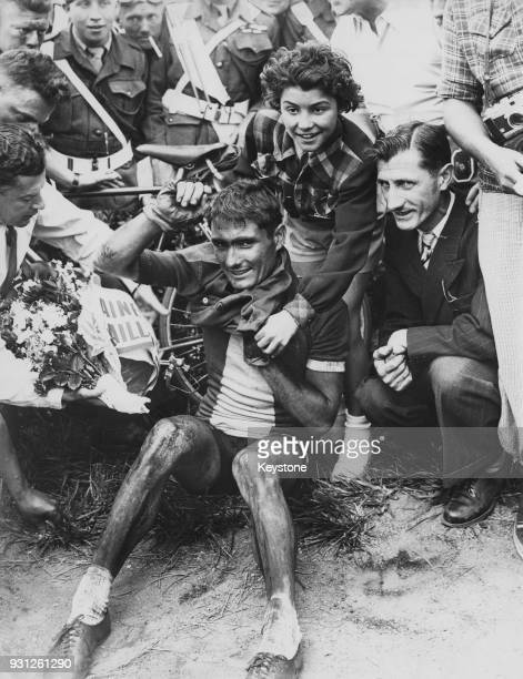 French child actor Roberto Benzi helps cyclist Bernard Gauthier into the yellow jersey after he led the general classification in the third lap of...