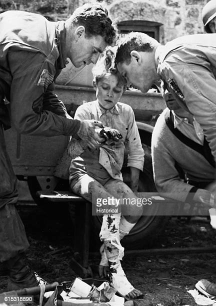 A French child injured when a German soldier threw a hand grenade into a group of Norman civilians is a brave patient as American medical corpsmen...