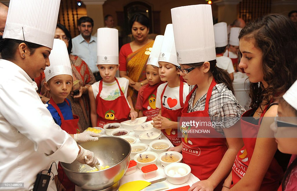 French children between the ages of six and twelve years old attend a special culinary session in New Delhi on May 29, 2010. The Imperial culinary club hosted the session teaching children to bake mouth watering recipes such as chocolate chip cookies, blueberry muffins and chocolate monginies.