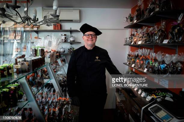 French chocolate maker and founder of the Criollo chocolate factory JeanPierre DujonLombard poses in his shop near chocolate creations made for the...