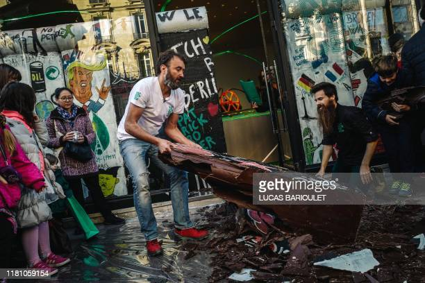 French chocolate maker Patrick Roger and one of his employee break a wall he made with chocolate to commemorate the 30th anniversary of the fall of...