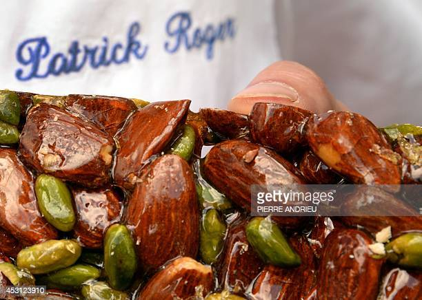 French chocolate maker Patrick Roger shows one if speciality caramelized almonds on August 2 in his workshop at Place de la Madeleine in Paris AFP...