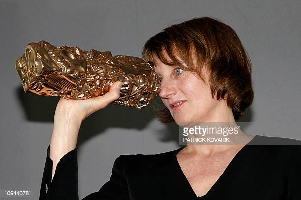 French cinematographer Caroline Champetier jokes with her trophy during a photocall after winning the Best Cinematography award for French director...