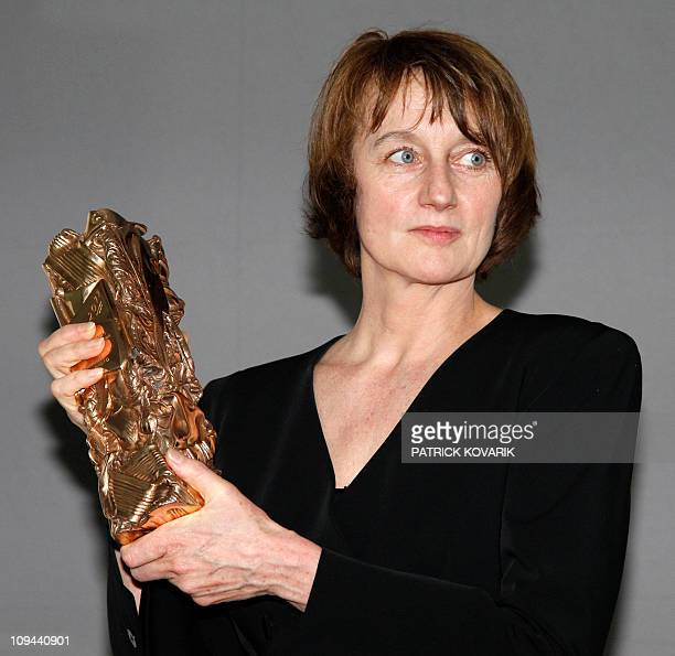 French cinematographer Caroline Champetier poses with her trophy during a photocall after winning the Best Cinematography award for French director...