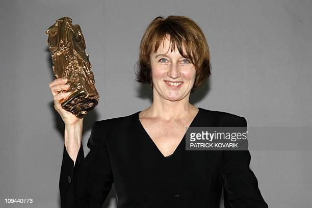 French cinematographer Caroline Champetier raises her trophy during a photocall after winning the Best Cinematography award for French director...