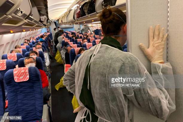 TOPSHOT French citizens arrive and settle aboard of an evacuation plane with destination southeastern France before departure from Wuhan Airport...