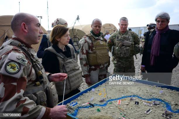 French Colonel of the Wagram Task Force FrancoisRegis Legrier explains military positions on a sand map to French Defence Minister Florence Parly...