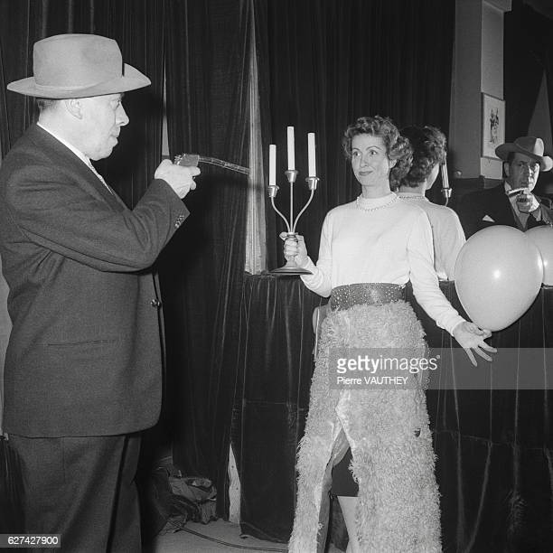 French comedian Fernandel points a toy gun at actress Danielle Darrieux during a performance in Paris Fernandel is attempting to shoot a balloon out...