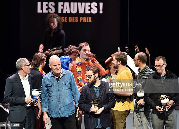 French comic book artist Etienne Davodeau and French writer and journalist Benoit Collombat pose on stage with other award winners after receiving...
