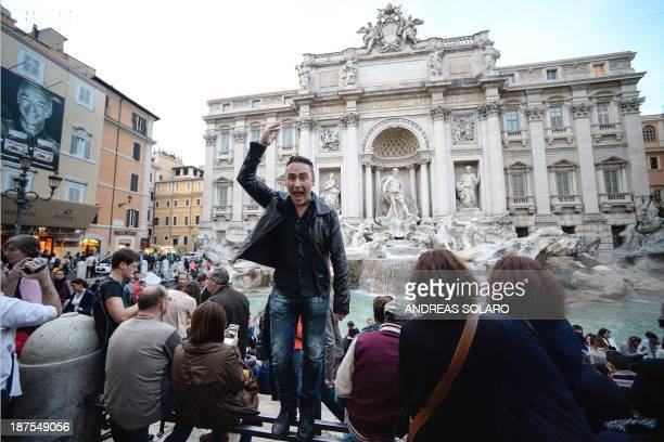 French comic strip writer Thierry Terrasson also known as Jim makes a wish as he throws a coin in the water of the Trevi Fountain on November 4 in...