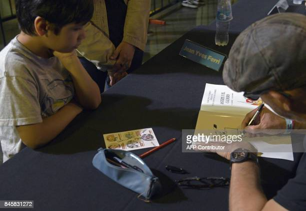 French comic writer designer and colourist JeanYves Ferri signs Argentine editions of Asterix and Obelix during the International Comic Festival...