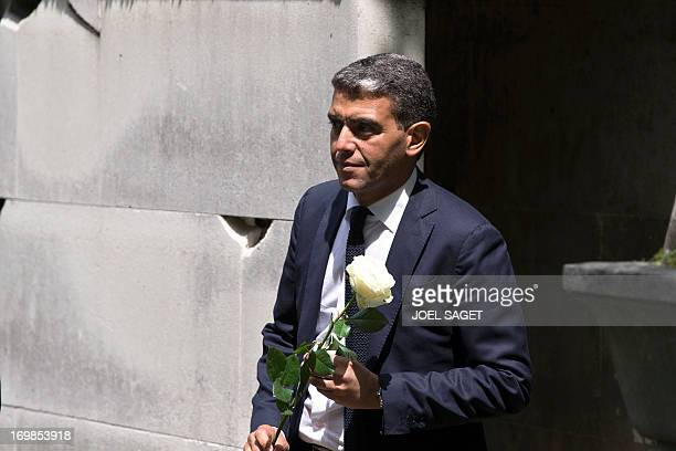 French Communication advisor Ramzi Khiroun carries a rose on June 3 2013 at the Montmartre cemetery in Paris during the funeral of the French...