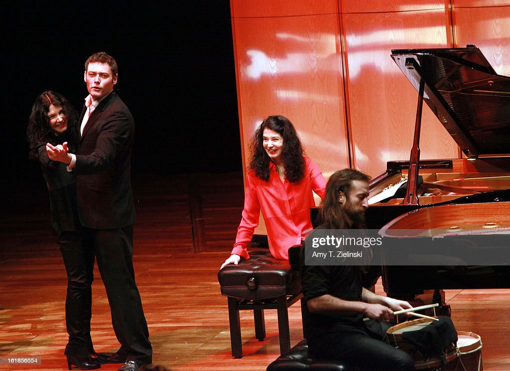 French concert pianist Katia Labeque (L) dances with the host while her sister Marielle Labeque (2nd-R) looks on before a performance with the Kalakan Trio on percussion Ravel's 'Bolero' arrangement for duo piano as part of 'Imagine' family concerts programming at the Queen Elizabeth Hall on February 17, 2013 in London, England. Jamixel Bereau (R) plays the drums.