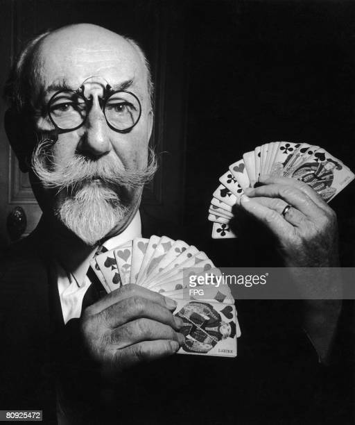 A French conjuror holds up a pair of fannedout hands of cards circa 1935