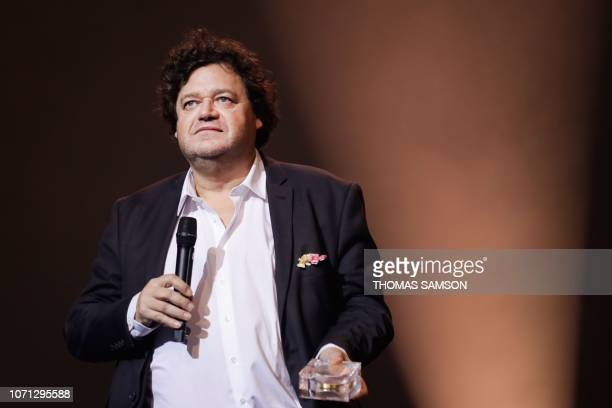 French conposer Philippe Schoeller celebrates after receiving the 'Symphony music' award during the SACEM Grand Prix awards ceremony on December 10...