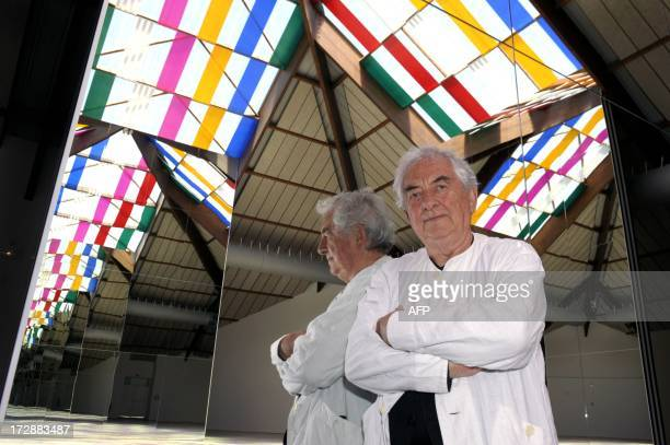 French contemporary artist Daniel Buren poses in front of his installation entitled Un bouquet 5 couleurs moins une travail in situ on July 5 2013 in...