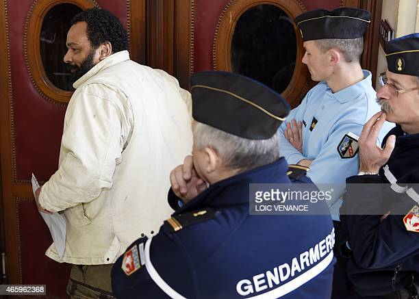 French controversial comic Dieudonne M'bala M'bala enters a courtroom in front of gendarmes at the Paris courthouse on March 12 for the trial of...