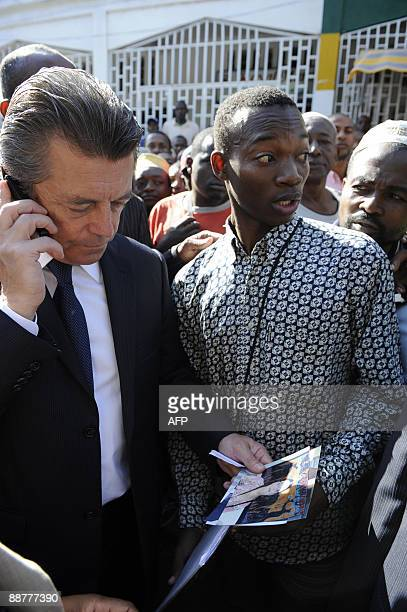 French Cooperation Minister Alain Joyandet looks at photos of a victims fiancee on July 1 2009 outside the El Maarouf de Moroni Hospital in the...