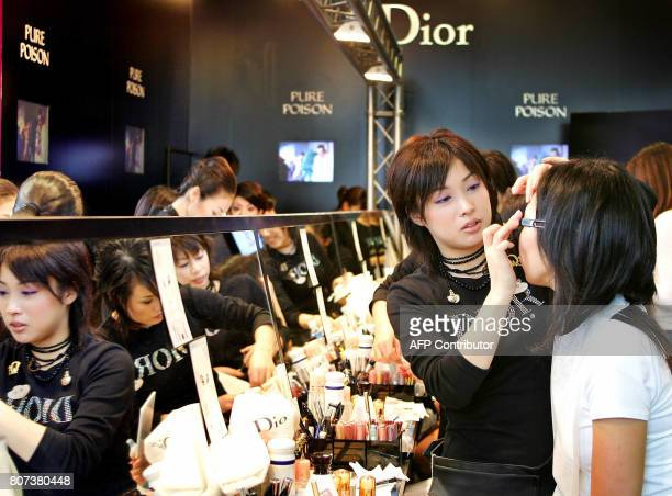 French cosmetics giant Christian Dior employees give free makeup services to customers during promotional sales for 'Pure Poison' perfume at Tokyo's...