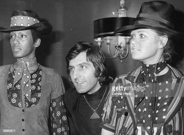 French couturier Emanuel Ungaro with two of his models wearing flower power daisy motifs, gypsy-style scarves and tall hats.