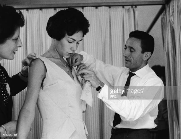 French couturier Guy Laroche adjusts the bodice of a model's dress during a fitting Paris 1960s