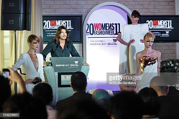 French couturier Stephane Rolland looks on as models presents his creations during a press conference for the Inaugural Women's Fashion Week 2011 in...