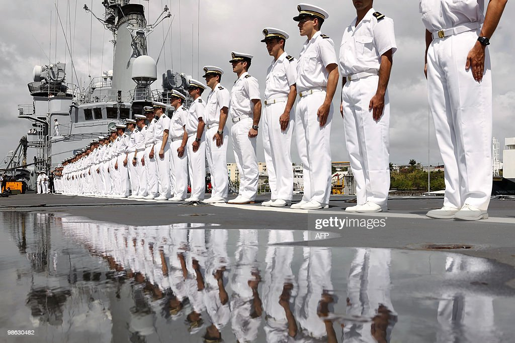 French crew members stand on March 22, 2010, on the deck of French helicopter-carrier Jeanne d'Arc, as it leaves Fort-de-France on the French island of La Martinique to Puerto Rico. The Jeanne d'Arc, built from 1959 to 1961, a 182-meter-long Naval Academy ship, carrying a crew of 585 officers and sailors, is on its last trip as a training vessel. AFP PHOTO