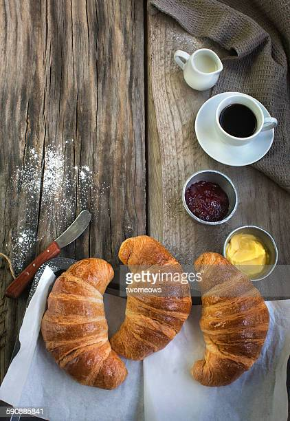 French croissants on wooden background.