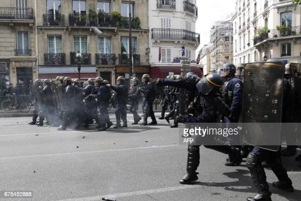 French CRS antiriot police officer throws a tear gas canister towards protesters during a march for the annual May Day workers' rally in Paris on May...